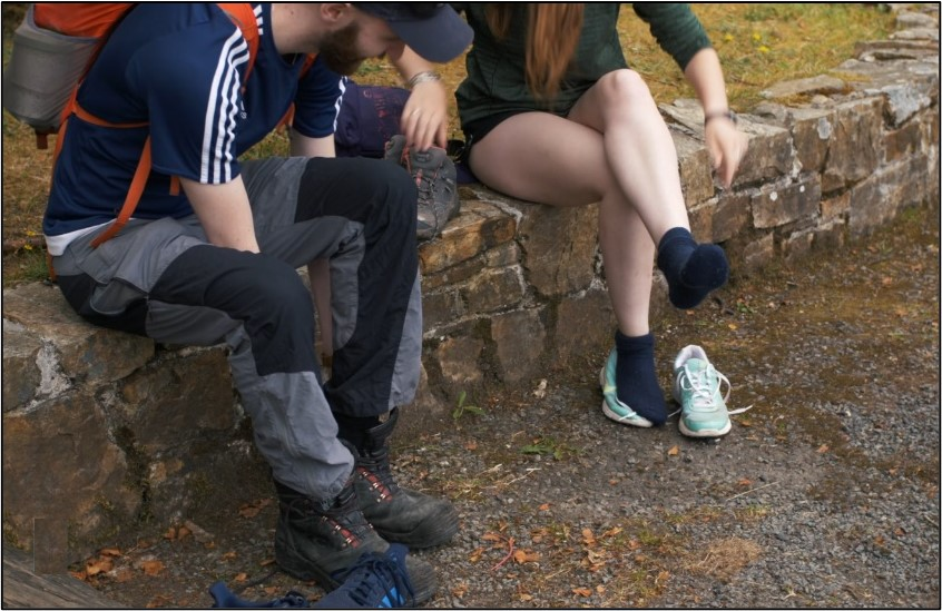 Pair of hikers putting on boots.