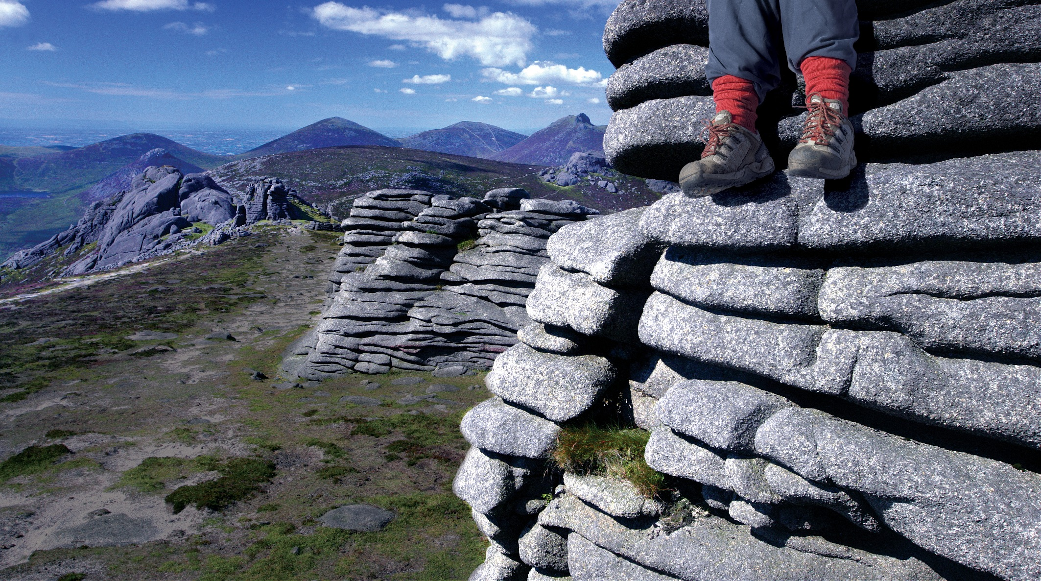 Legs overhanging from a rock showing their hiking boots