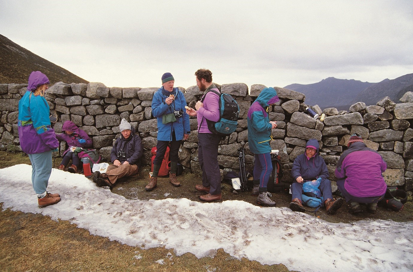 Group of hikers sitting next to wall up Mourne Mountains with snowfall